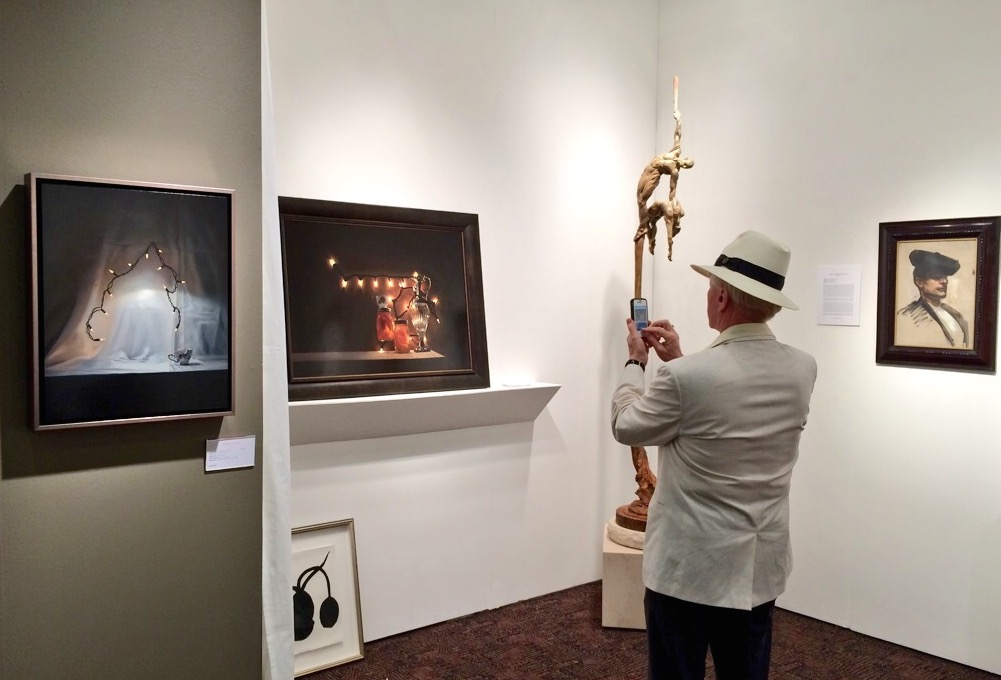 A visitor photographs works by Tom Betts at the Palm Springs Fine Art Fair 2015; installation view of Dawson Cole Fine Art with works by Tom Betts, Donald Sultan, Richard MacDonald, and John Singer Sargent; photo © codylee.co