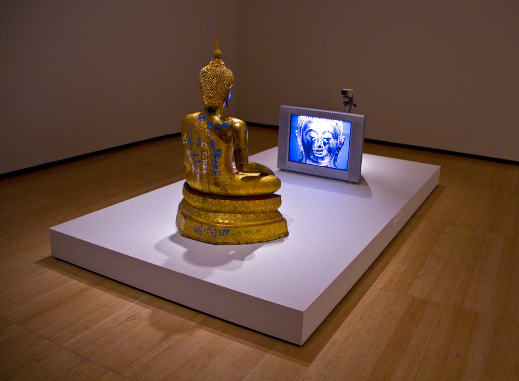 Nam June Paik, Golden Buddha, 2005; video installation with 27-inch monitor and closed circuit video camera, painted bronze Buddha with the artist's additions in permanent oil marker; installation view at Gagosian Gallery at Art Basel in Hong Kong 2015; image © Art Basel