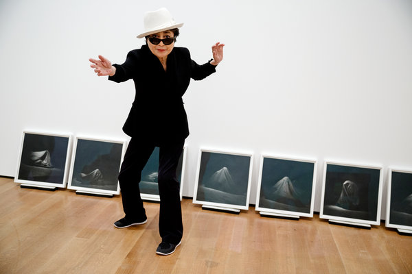 Yoko Ono at MoMA in front of photographs of a 1965 performance of Bag Piece; photo credit Richard Perry for The New York Times