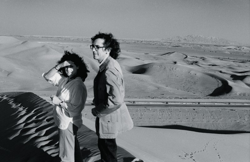 February 1979. Christo and Jeanne-Claude survey the desert from their vantage on top of a dune in the UAE desert. In the background are the Al Hajah mountains. Photo: Wolfgang Volz © 1979 Christo
